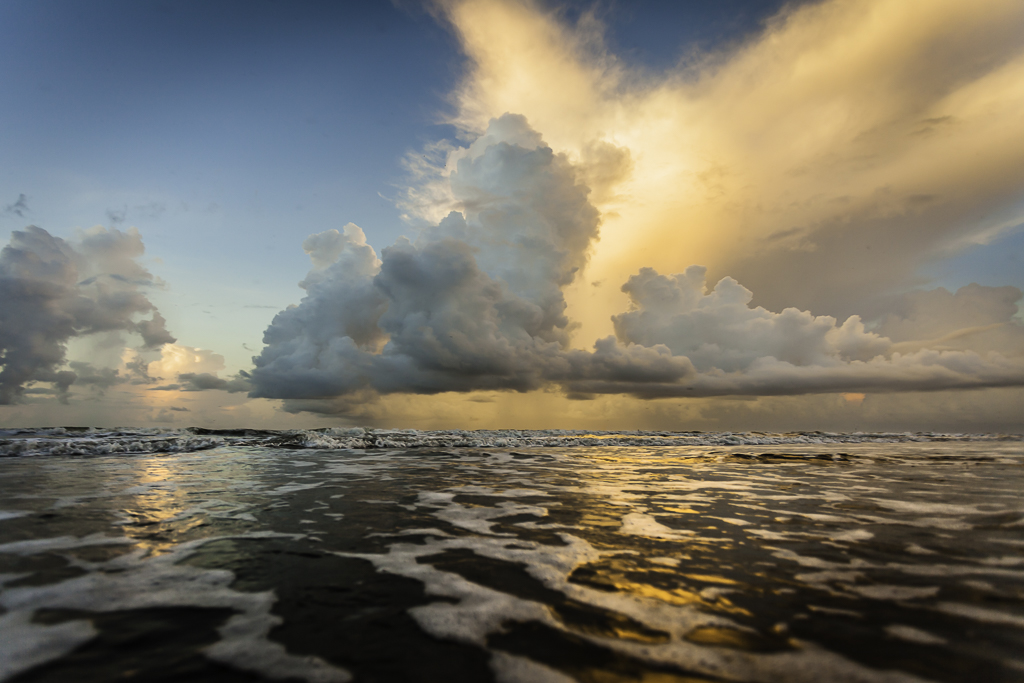 A seascape photograph of a sunrise over Surfside Beach, Texas, USA.