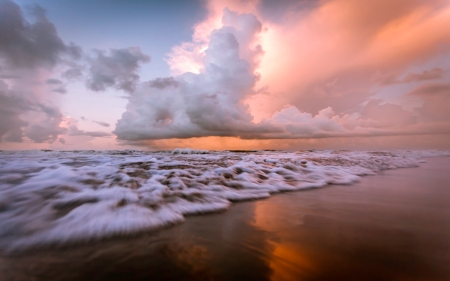 A seascape photograph of a sunrise over Surfside Beach, Texas, USA.